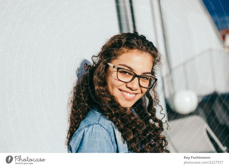 Smiling woman with curly hair and glasses leaning against the house wall Lifestyle Joy Happy Beautiful Hair and hairstyles Well-being Contentment Feminine