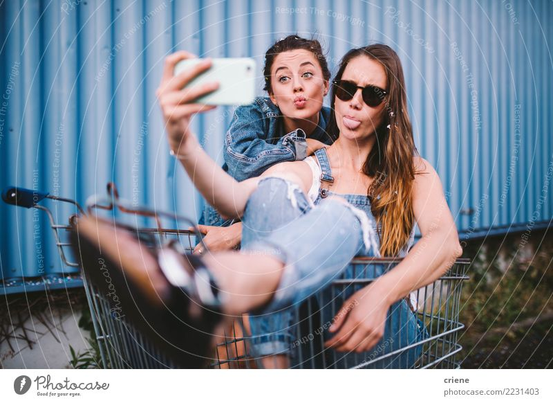 Young adult hipster girlfriends taking selfie and pulling faces Lifestyle Shopping Joy Happy Face Leisure and hobbies Summer Telephone Technology Woman Adults