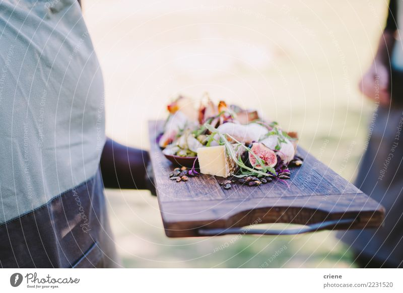 Waiter serving cheese platter in restaurant Cheese Eating Diet Restaurant Wood Fresh Delicious board waiter food wine Fig Delicatessen Diary Colour photo