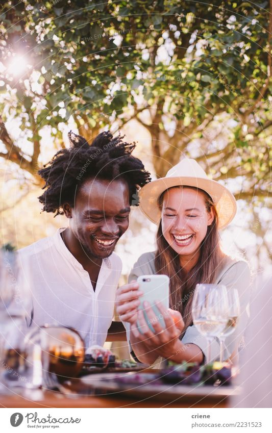 Happy Young adult couple watching videos on phone Lifestyle Joy Summer Table Restaurant Telephone Technology Couple Adults Afro Smiling Together Bright Emotions