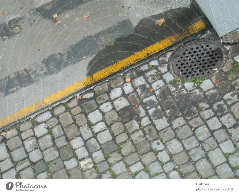 Street Signs and labeling Floor covering Asphalt Cobblestones Parking lot Gully Drainage