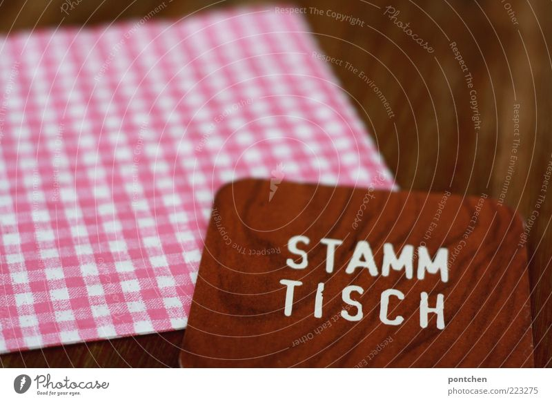 Beer mat with imprint Stammtisch on checked napkin and wooden table Table Village Characters Esthetic Exceptional Uniqueness Kitsch Brown Pink