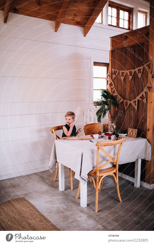 Cute little boy eating christmas candy and wrapping gifts Eating Winter Table Living room Child Boy (child) Infancy Hut Sit sweets holiday Santa Claus
