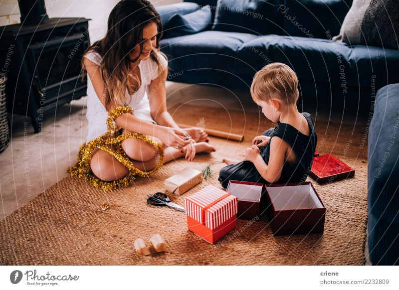 Young family wrapping Christmas gifts at home Child Human being Christmas & Advent Joy Winter Adults Family & Relations Happy Together Infancy Creativity Mother