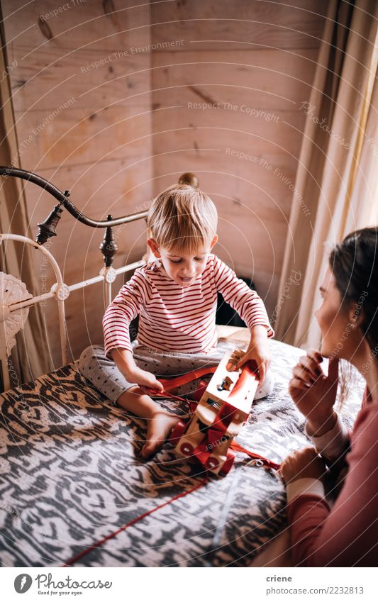 Llittle boy sitting on bed opening christmas gifts with mother Child Woman Human being Youth (Young adults) Christmas & Advent House (Residential Structure) Joy