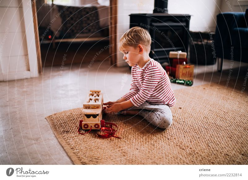 Toddler boy playing with new toy wearing pyjamas Lifestyle Joy Happy Leisure and hobbies Playing Winter House (Residential Structure) Living room