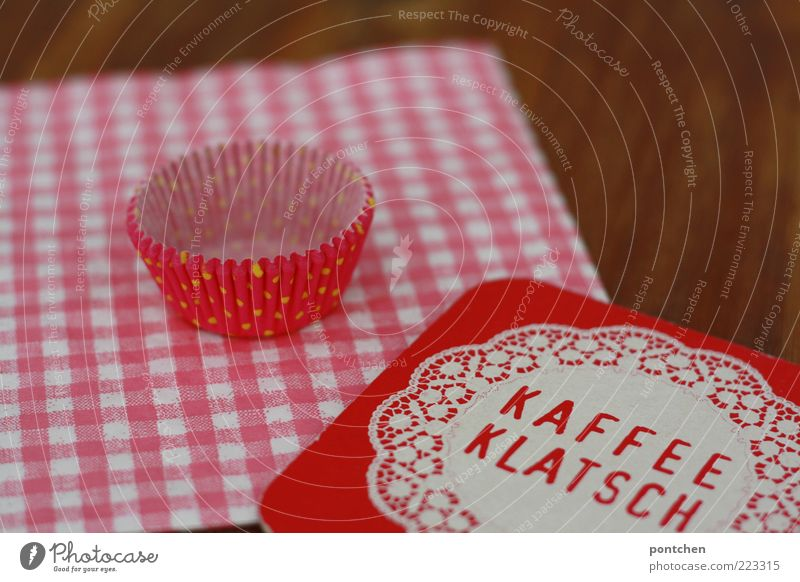 Beer mat with imprint Kaffeeklatsch on pink checked napkin and wooden table. Cupcake mould Style Esthetic Hip & trendy Kitsch Brown Pink Coffee break papery