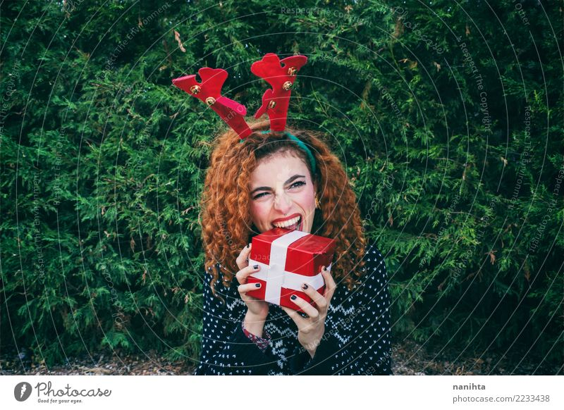 Young woman eating a christmas gift Human being Nature Youth (Young adults) Christmas & Advent Plant Beautiful Green Tree Red Joy Winter 18 - 30 years Adults