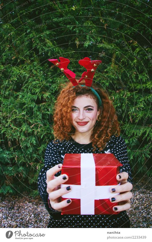 Young woman holding a christmas gift box Human being Nature Youth (Young adults) Christmas & Advent Beautiful Tree Joy Winter 18 - 30 years Adults Life