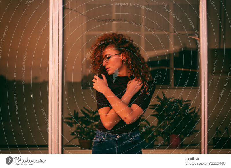 Young woman hugging herself Human being Youth (Young adults) Plant Beautiful Loneliness Calm Window 18 - 30 years Adults Lifestyle Feminine Brown Orange Retro