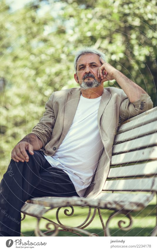 Pensive mature man sitting on a bench in an urban park. Lifestyle Happy Retirement Human being Masculine Man Adults Male senior 1 45 - 60 years