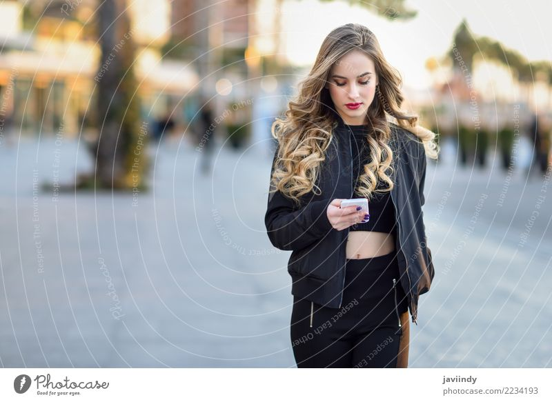 Woman texting with her smart phone in urban background Human being Youth (Young adults) Young woman Beautiful White 18 - 30 years Adults Street Lifestyle Autumn
