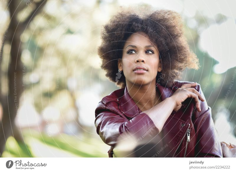 Black woman with afro hairstyle sitting in an urban park Woman Human being Youth (Young adults) Young woman Beautiful White Red 18 - 30 years Face Adults Street