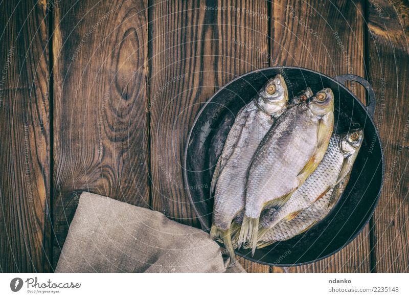 fish ram in a round black frying pan Fish Seafood Plate Pan Ocean Kitchen Nature Animal Wood Natural Above Brown Roach salted background dry Preparation Snack