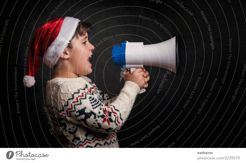 boy with a megaphone at christmas on black background Lifestyle Joy Entertainment Party Event Feasts & Celebrations Christmas & Advent New Year's Eve