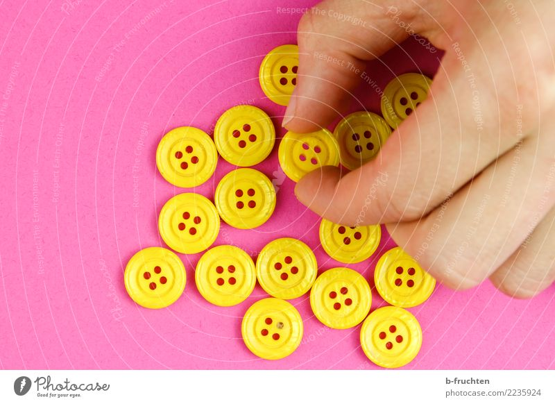 Yellow buttons Man Adults Hand Fingers To hold on Pink Select Take Buttons majority Selection Many Colour photo Interior shot Close-up Copy Space left Downward