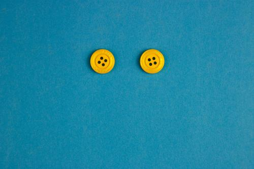 buttonhole monster Plastic Sign Blue Yellow Joy Contentment Buttons Eyes Face 2 In pairs Looking Smiley Interior shot Studio shot Close-up Deserted