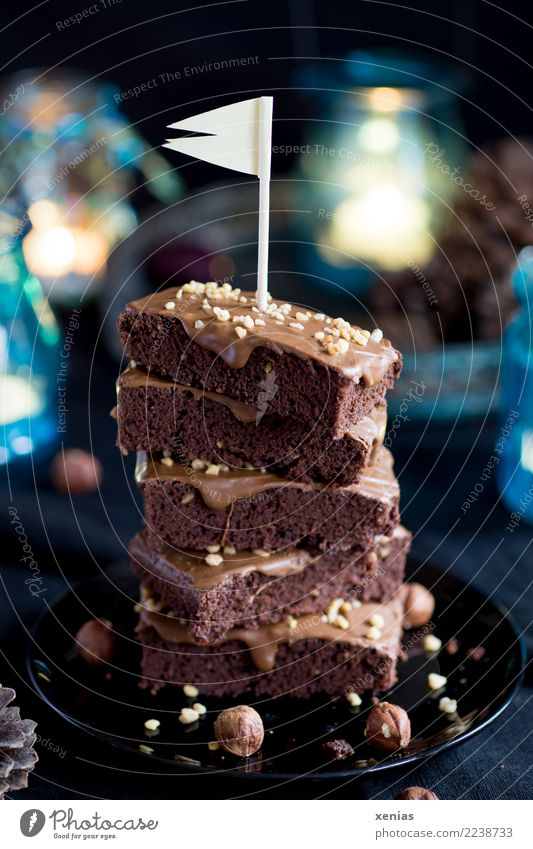 piled up chocolate cake with hazelnut and flag on a black plate with blue lights in the background Cake Chocolate brownie Chocolate cake Hazelnut hazelnut cream