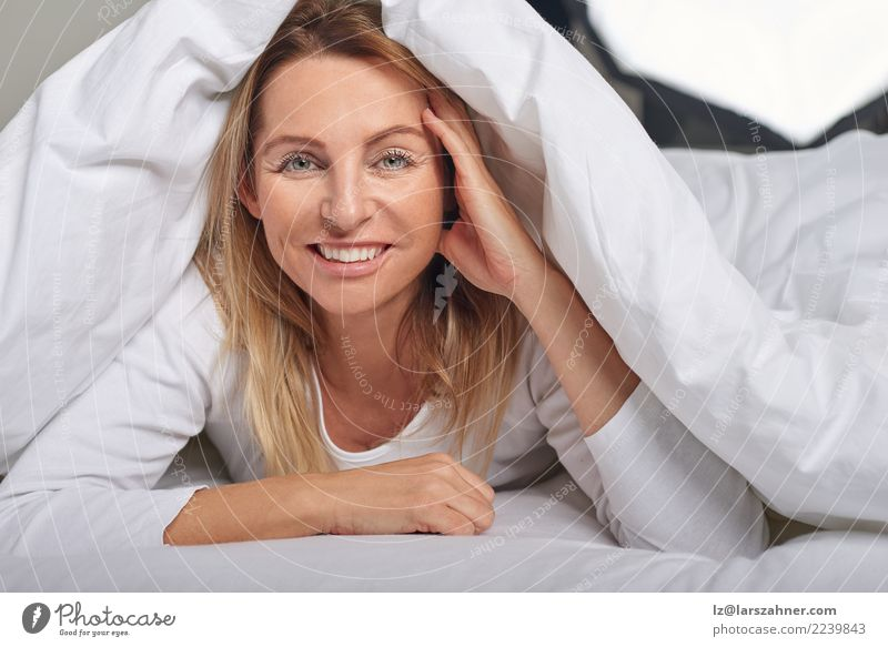 Beautiful middle-aged woman under sheets Happy Skin Face Relaxation Bedroom Woman Adults 1 Human being 45 - 60 years Blonde Smiling Sleep Happiness Under Soft