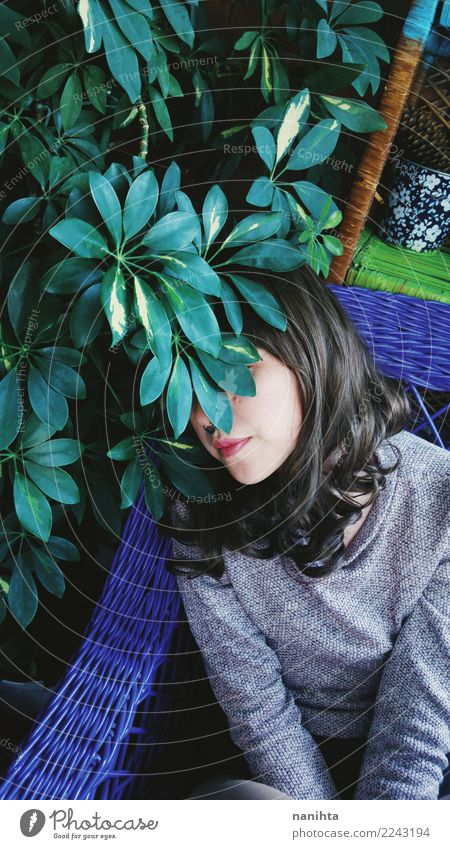 Young woman hidden behind a plant Lifestyle Style Exotic Senses Relaxation Interior design Sofa Attic Human being Feminine Youth (Young adults) 1 18 - 30 years