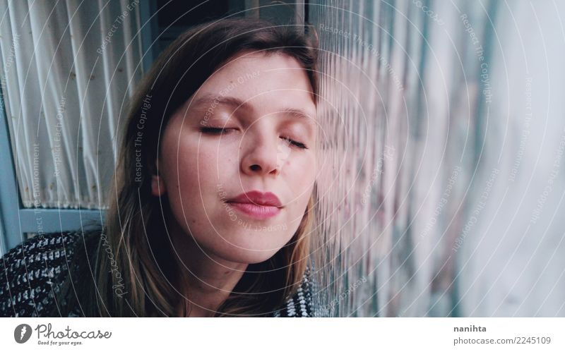 Young happy woman leaning against a window Human being Youth (Young adults) Young woman Blue White Relaxation Window 18 - 30 years Face Adults Lifestyle Cold