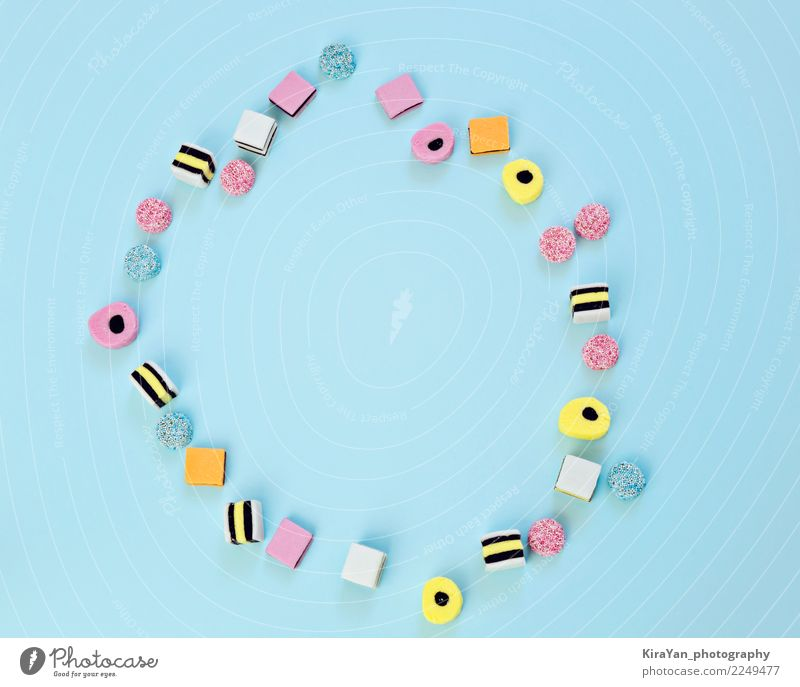 Colored sweets are scattered on a blue background Blue Colour Red Joy Eating Yellow Art Playing Food Feasts & Celebrations Group Pink Copy Space Birthday