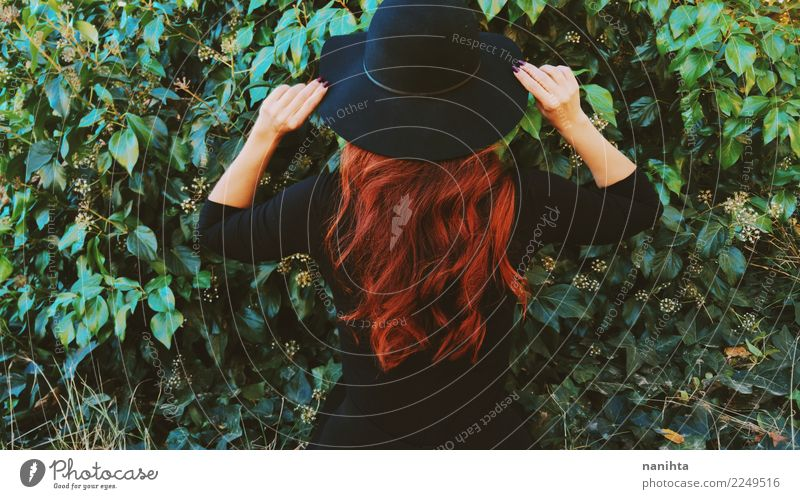 Back view of a redhead woman in a green garden Woman Human being Nature Plant Green Red Leaf Dark Black Adults Lifestyle Feminine Style Garden