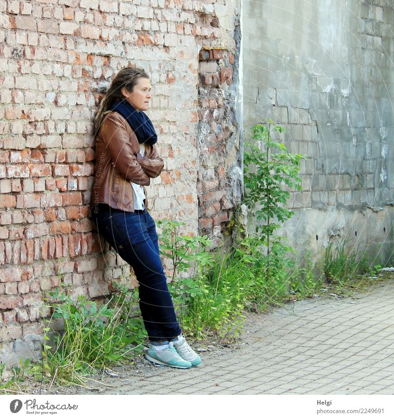 thoughtful woman with dreadlocks, in jeans and brown leather jacket is standing at an old dilapidated house wall Human being Feminine Woman Adults 1