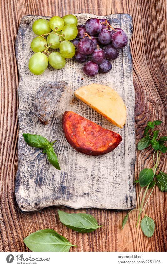 Cheese and grapes decorated on handmade pottery plate Food Fruit Nutrition Breakfast Lunch Plate Table Wood Rust Fresh Delicious Above Basil ceramic Cooking