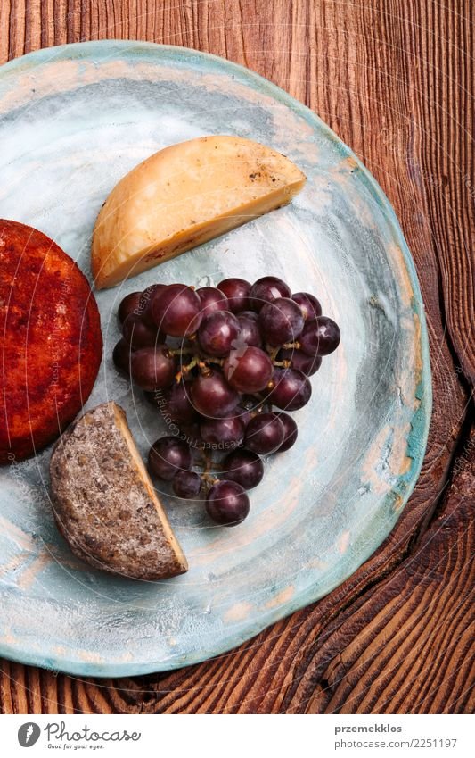 Cheese and black grapes on handmade blue pottery plate Food Fruit Breakfast Plate Table Wood Rust Fresh Delicious Above ceramic Cooking Gourmet Bunch of grapes