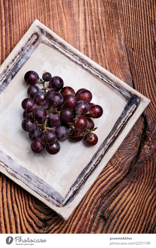 Black grapes on handmade square pottery plate Wood Food Above Fruit Fresh Table Delicious Rust Plate Cooking Diet Sense of taste Rustic Snack Bunch of grapes