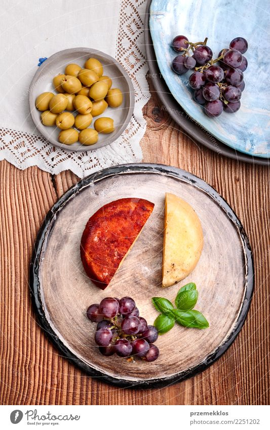 Cheese and black grapes on handmade pottery plate Food Fruit Nutrition Breakfast Plate Table Wood Rust Fresh Delicious Above ceramic Cooking Gourmet