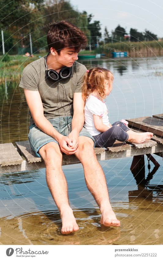 Young boy and his little sister sitting on jetty over the lake and dipping feet in water on sunny day in the summertime Lifestyle Joy Happy Relaxation