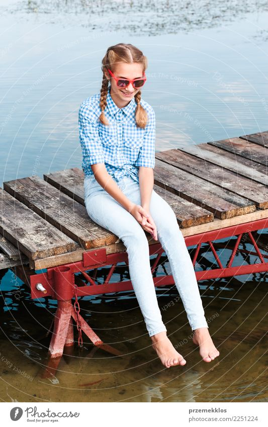 Girl sitting on jetty over the lake and dipping feet in water Human being Vacation & Travel Youth (Young adults) Young woman Summer Relaxation Joy Lifestyle