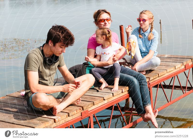 Family spending vacation time together sitting over the lake Child Woman Human being Vacation & Travel Youth (Young adults) Young woman Summer Young man