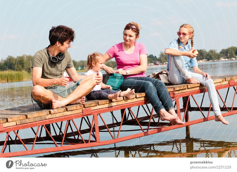 Family spending vacation time together having a snack sitting on jetty over the lake on sunny day in the summertime Joy Happy Relaxation Leisure and hobbies