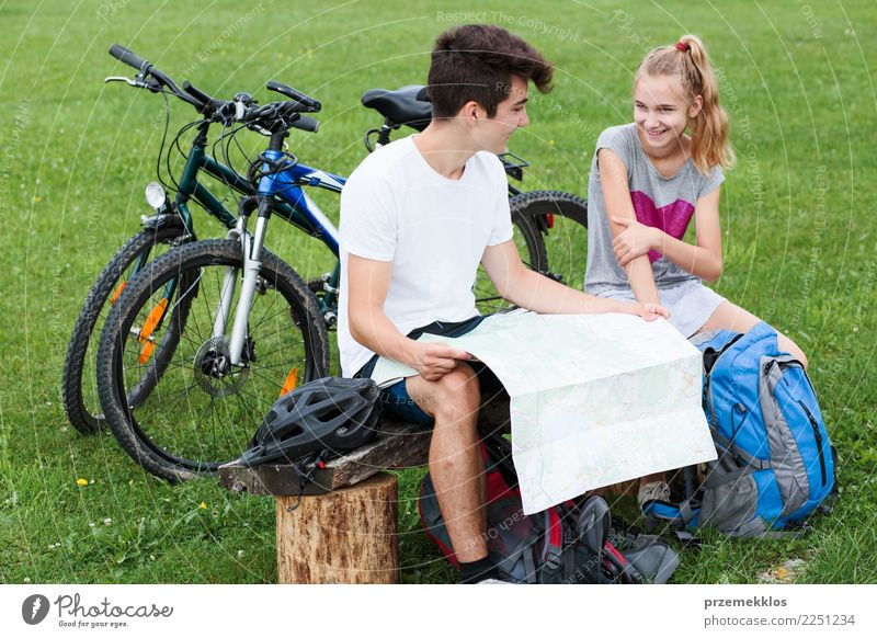 Boy and girl having a break sitting on bench during bike trip Lifestyle Leisure and hobbies Vacation & Travel Trip Adventure Summer Cycling Child Girl