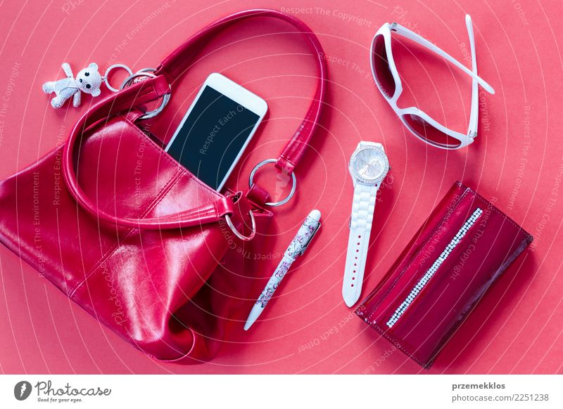 Red and white things pulled out of red handbag Lifestyle Elegant Style Contentment Telephone Cellphone PDA Accessory Pen Observe Above glasses Handbag key