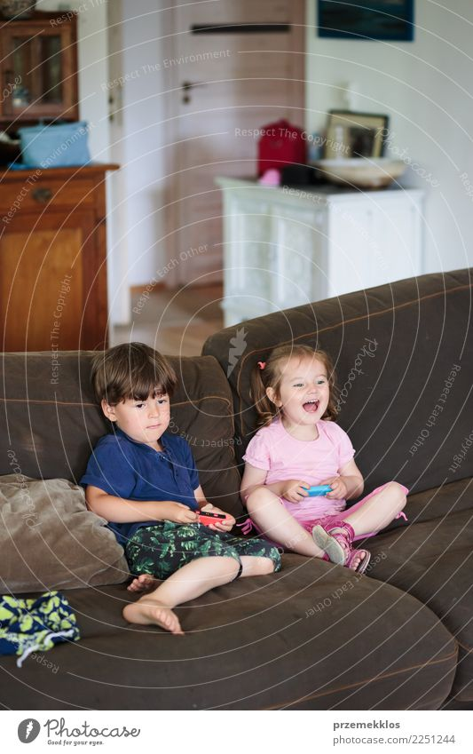 Toddlers boy and girl playing video game sitting on sofa at home Child Human being Joy Girl Lifestyle Family & Relations Boy (child) Small Happy Playing