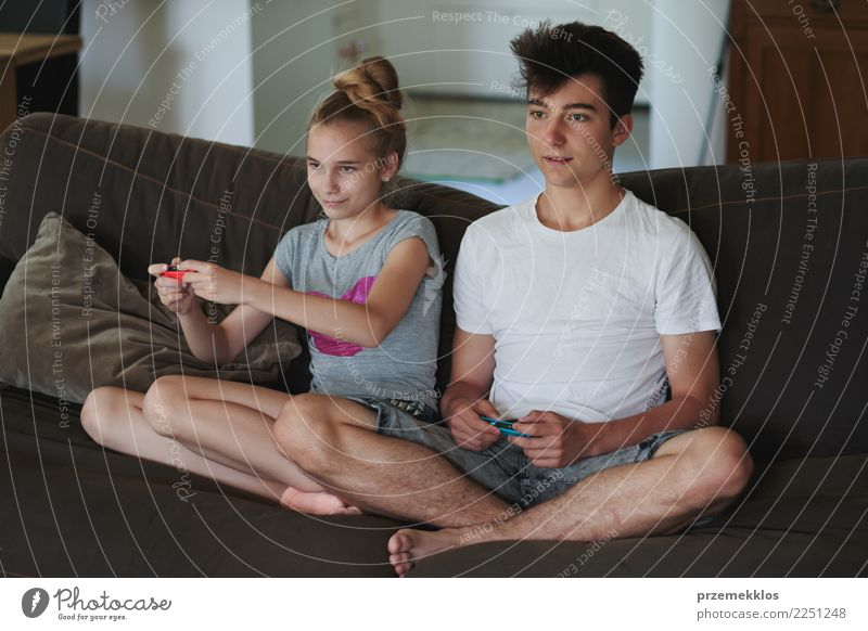 Boy and girl playing video games sitting on sofa at home Child Human being Youth (Young adults) Young woman Young man Joy Girl Lifestyle Family & Relations