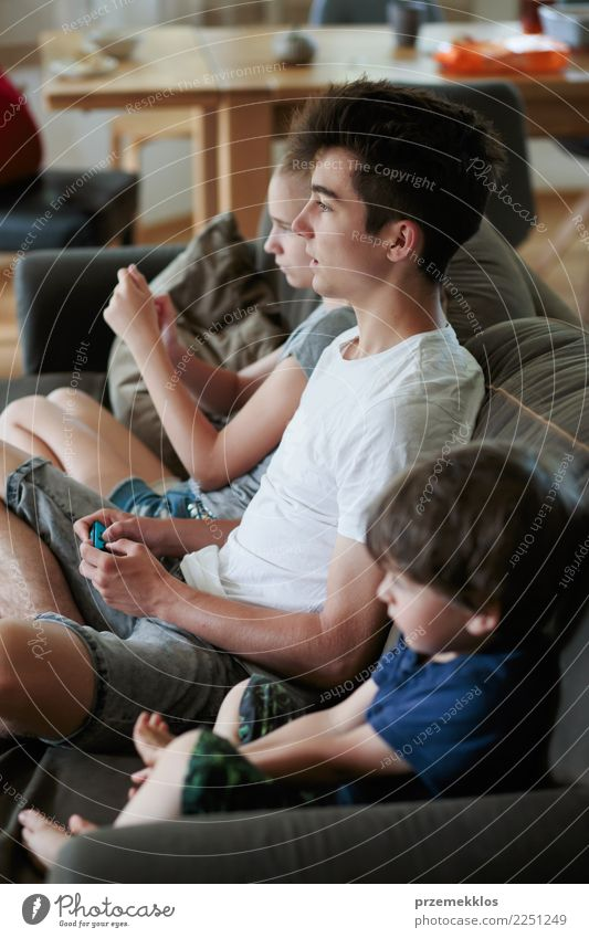 Concentrated young boy and girl playing video games sitting on sofa at home Lifestyle Joy Leisure and hobbies Playing Sofa Child Technology Toddler Girl