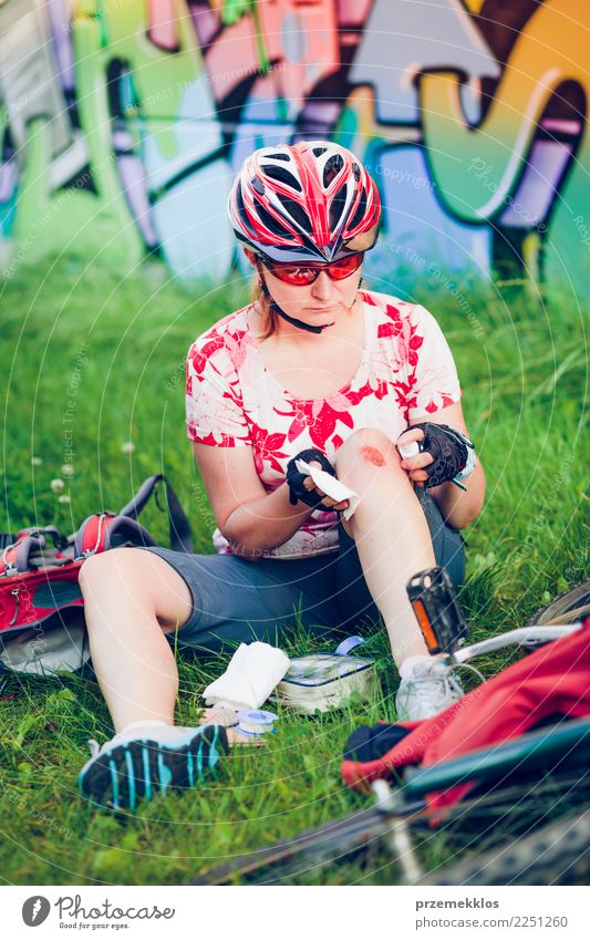 Woman dressing the wound on her knee with medicine in spray Lifestyle Vacation & Travel Summer Sports Cycling Human being Adults Grass Pain accident Action