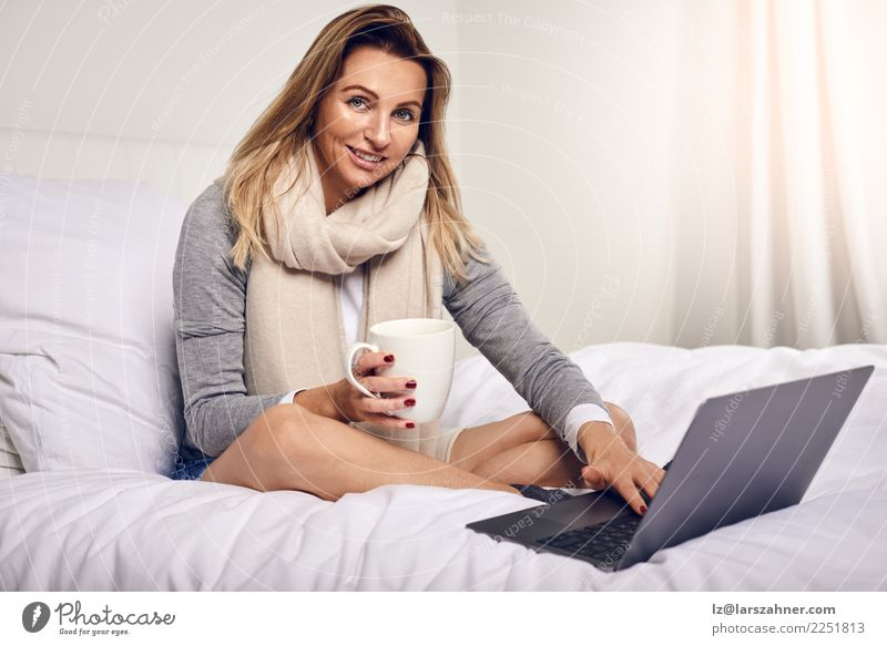 Attractive woman sitting on her bed with coffee Coffee Tea Lifestyle Shopping Happy Contentment Bedroom Work and employment Computer Notebook Technology