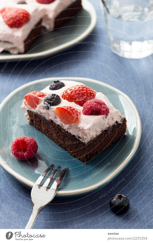 Brownie with berries and cream on a blue plate, with cake fork and a glass of water Cake fruit Baked goods brownie Strawberry Raspberry Blueberry Cream Sugar