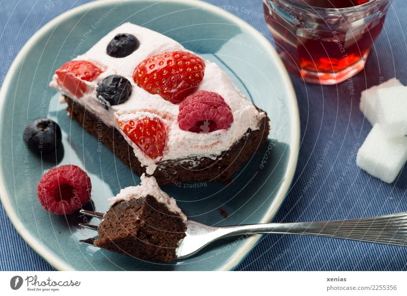 The essential in the afternoon - chocolate cake with cream and berries on a blue plate, served with red tea with sugar cubes Cake Chocolate Raspberry Fruit
