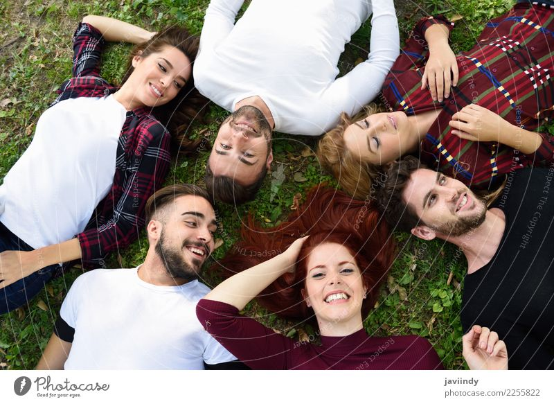 Women and men laying on grass wearing casual clothes. Woman Human being Youth (Young adults) Man Young woman Beautiful Young man Joy 18 - 30 years Street Adults