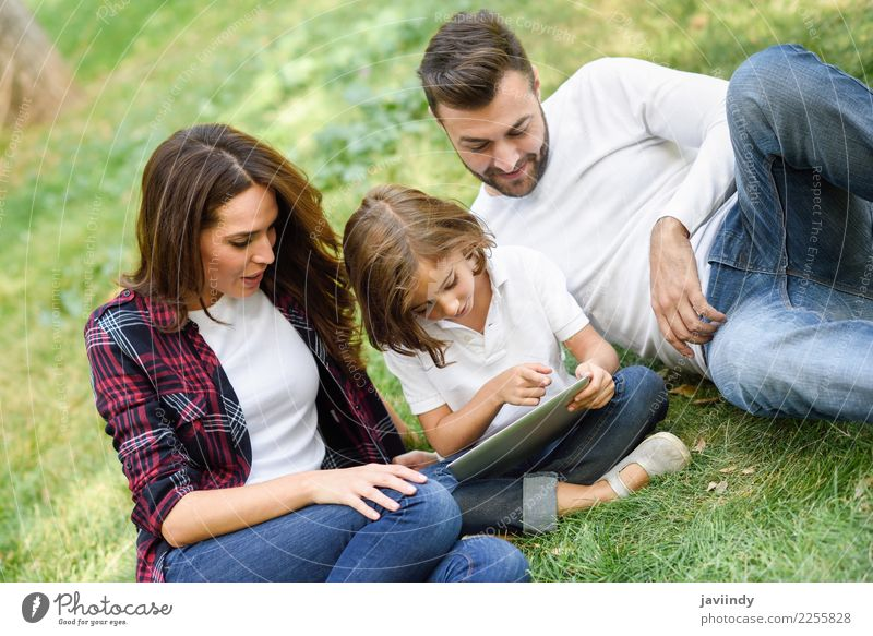 Happy family in a urban park playing with tablet compute Child Woman Human being Youth (Young adults) Man Young woman Summer Beautiful Young man Joy Girl