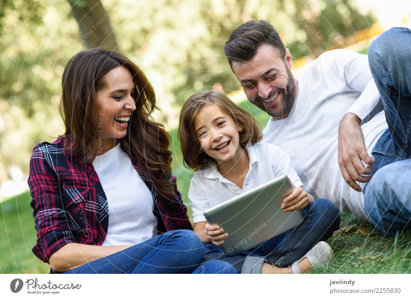 Happy family in a urban park playing with tablet computer Child Woman Human being Youth (Young adults) Man Young woman Summer Beautiful Young man Joy Girl