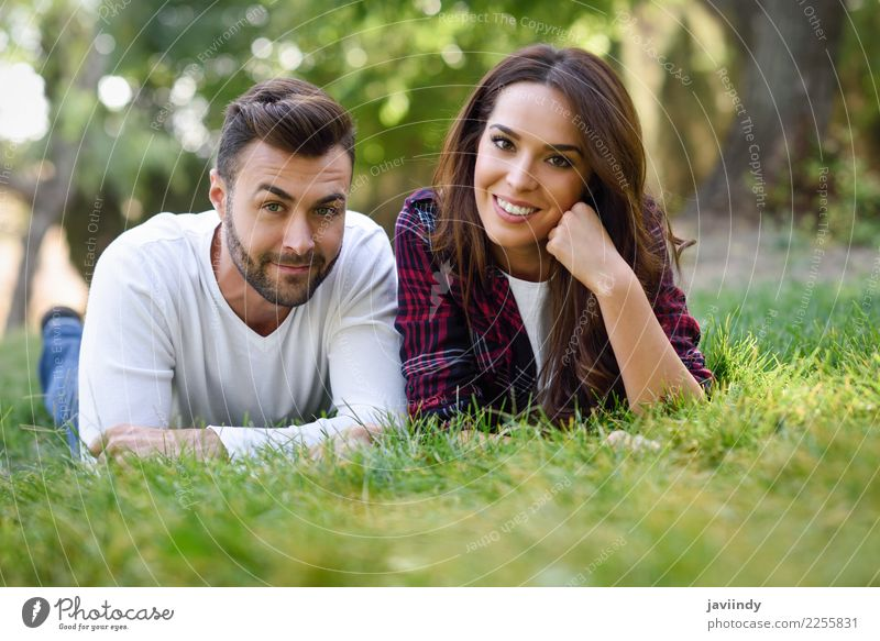 Beautiful young couple laying on grass in an urban park Woman Human being Nature Youth (Young adults) Man Young woman Summer Green Young man Joy 18 - 30 years