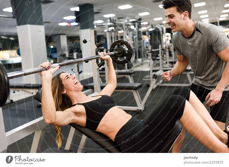 Personal trainer motivating a young woman lift weights Lifestyle Body Sports Human being Masculine Feminine Young woman Youth (Young adults) Young man Woman